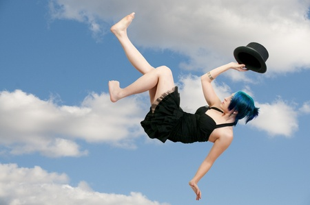 A beautiful young actress dancer wearing a top hat flying through the air photo