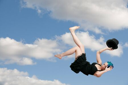 A beautiful young actress dancer wearing a top hat flying through the sky or falling through the air photo