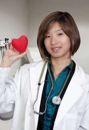 sexy asian woman: An Asian female cardiologist holding a red heart