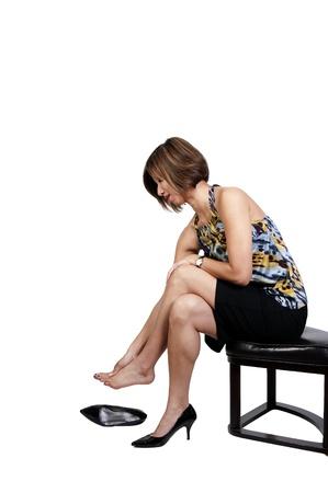 Een mooie jonge vrouw wreef over haar pijnlijke vermoeide voeten