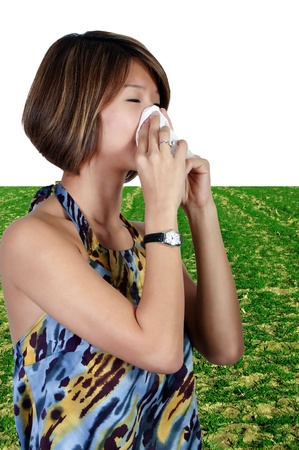A beautiful Asian woman with a cold, hay fever or allergies blowing her nose photo