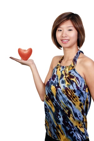 A young Beautiful Asian Woman holding a healthy heart shaped apple photo