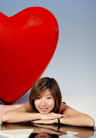 matchmaker: A big red heart behind a beautiful young Asian woman