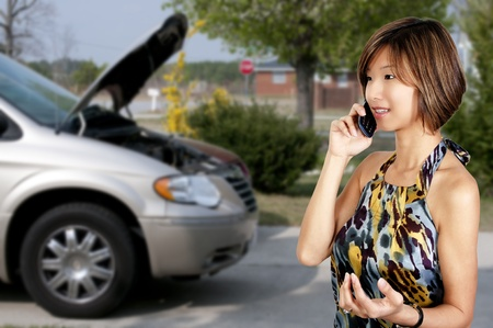 A woman with car trouble calling for help photo