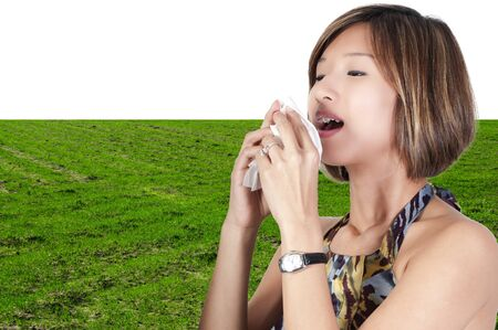 A beautiful Asian woman with a cold, hay fever or allergies blowing her nose Stock Photo - 9582923