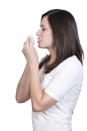 A beautiful woman with a cold, hay fever or allergies blowing her nose Stock Photo - 9582555