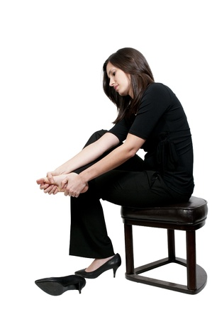 foot pain: A beautiful young business woman rubbing her sore tired feet Stock Photo