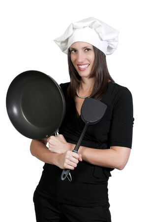 A beautiful young woman chef holding a spatula and frying pan photo