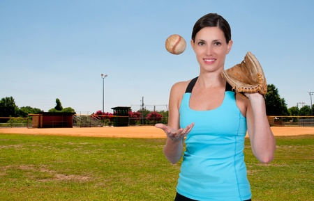 A beautiful woman throwing a baseball into the air at a ball field