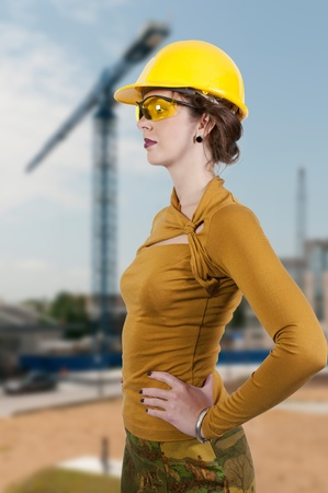 A Female Construction Worker wearing a hard hat and safety glasses photo