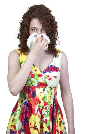 A beautiful woman with a cold, hay fever or allergies blowing her nose Stock Photo - 9582565