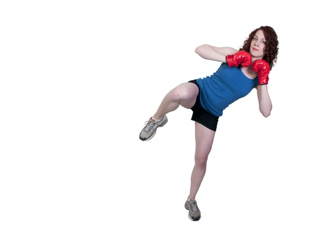 A beautiful young woman practicing martial arts kickboxing photo
