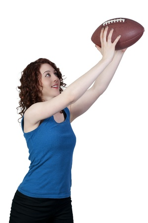 A beautiful young woman catching a football photo