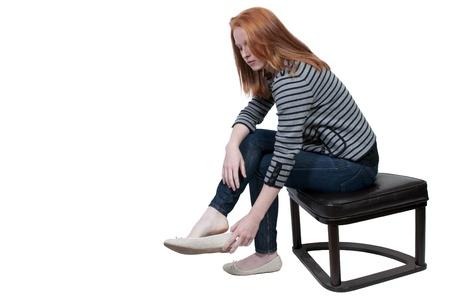 Een mooie jonge vrouw die op haar schoenen Stockfoto