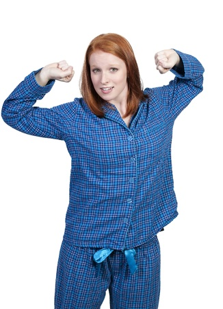 A young stretching woman waking up in her pajamas in the morning photo