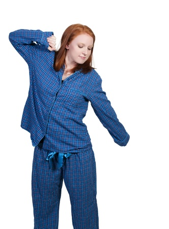 A young stretching woman waking up in her pajamas in the morning Banco de Imagens