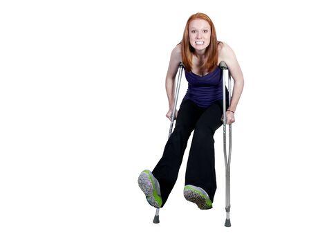 disability insurance: Una bella donna utilizzando una serie di stampelle medicale di aiutarla a piedi Archivio Fotografico