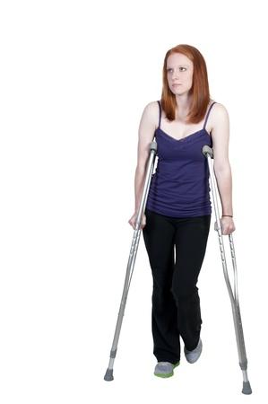disability insurance: Una bella donna utilizzando un set di stampelle medici per aiutare il suo cammino Archivio Fotografico
