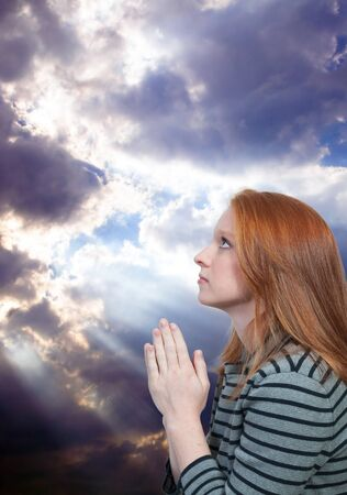 woman kneeling: Beautiful Christian woman in a deep prayer Stock Photo