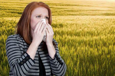 alergenos: Una hermosa mujer con un resfriado, fiebre del heno o alergias soplando su nariz