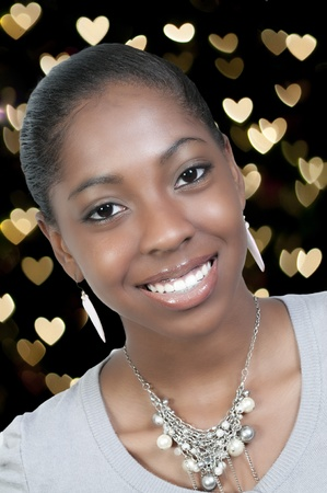 african woman face: A very beautiful African American black woman teenager with a big smile with heart bokeh