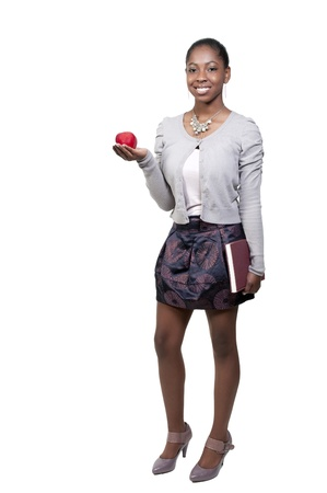 A very beautiful African American black woman teenage student holding a book and an apple Stock Photo - 9779275