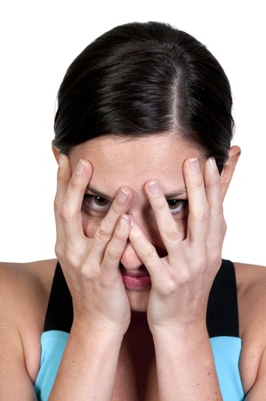 A beautiful young scared or surprized woman looking through her hands Stock Photo