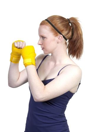 Een mooie jonge vrouw die een paar bokshandschoenen Stockfoto