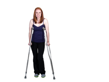 A beautiful woman using a set of medical crutches to help her walk photo