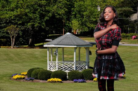 An African American teenage girl at a gazebo in a front yard with flowers photo