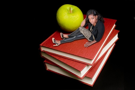 Back to School Concept - A teacher or teenager woman sitting beside an apple on a book. photo