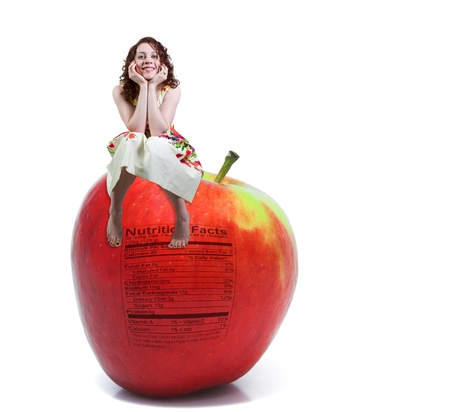 A beautiful young woman sitting on a whole red delicious apple with a nutrition label photo