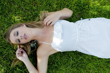 A beautiful young woman laying in a grassy yard Stock Photo - 10196324
