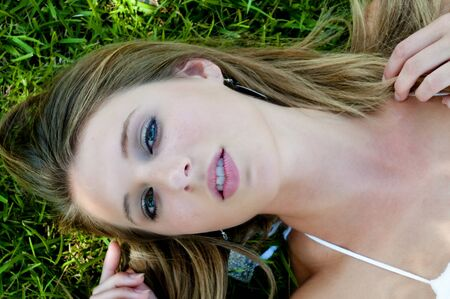 A beautiful young woman laying in a grassy yard photo
