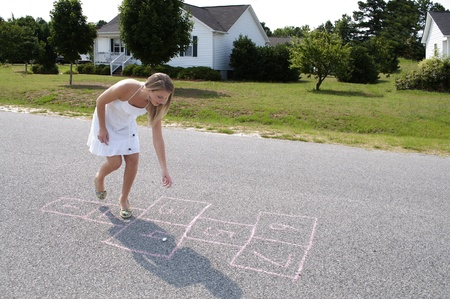 hopscotch: A beautiful woman engaged in the childhood game of hopscotch Stock Photo
