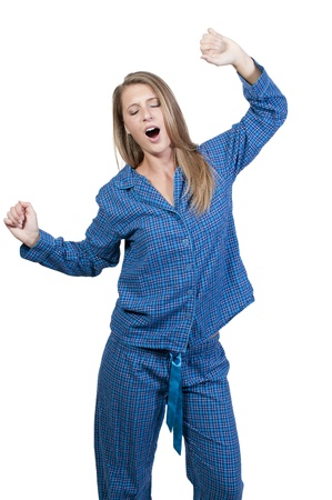 A young yawning and stretching woman waking up in her pajamas in the morning photo