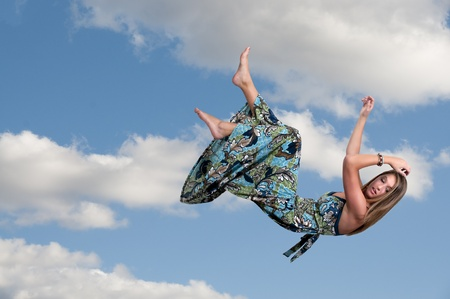 A beautiful young woman falling through the sky photo