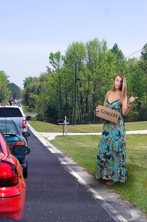 A beautiful woman with a sign hitch hiking to a concert Stock Photo - 10197443