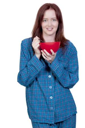 A beautiful woman wearing pajamas eating food from a bowl Stok Fotoğraf