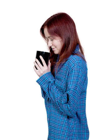 night shirt: A beautiful young woman drinking and smelling coffee in her pajamas