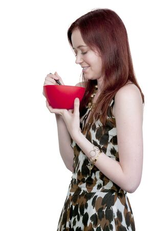 A beautiful woman eating food from a bowl photo