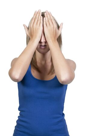 A beautiful young scared or surprized woman covering her eyes with her hands photo