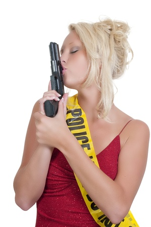 A beautiful police detective woman on the job kissing her gun photo
