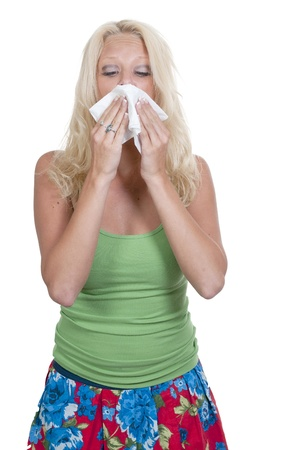 A beautiful woman with a cold, hay fever or allergies blowing her nose photo