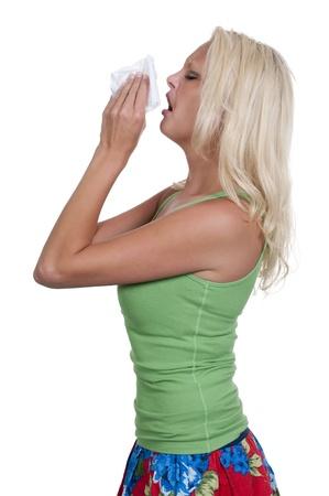 Een mooie vrouw met een koude, hooikoorts of allergieën blazen haar neus