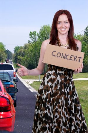 A beautiful woman with a sign hitch hiking to a concert Stock Photo - 10258939