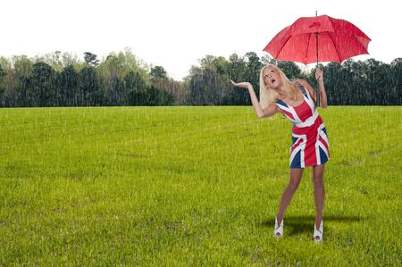 downpour: A beautiful young woman holding an umbrella in the rain Stock Photo