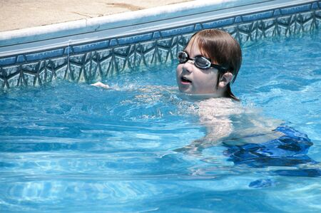 A little boy swimming in a pool. photo