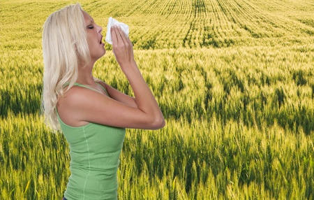 A beautiful woman with a cold, hay fever or allergies blowing her nose Stock Photo - 10258627