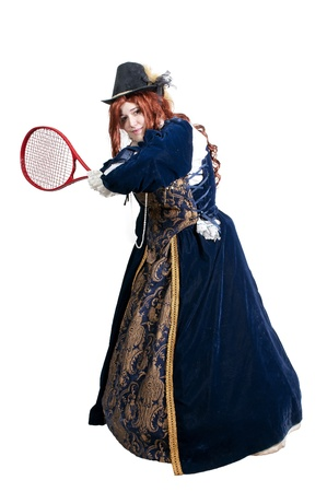 A woman dressed as a renaissance aristocrat in authentic dress playing tennis photo